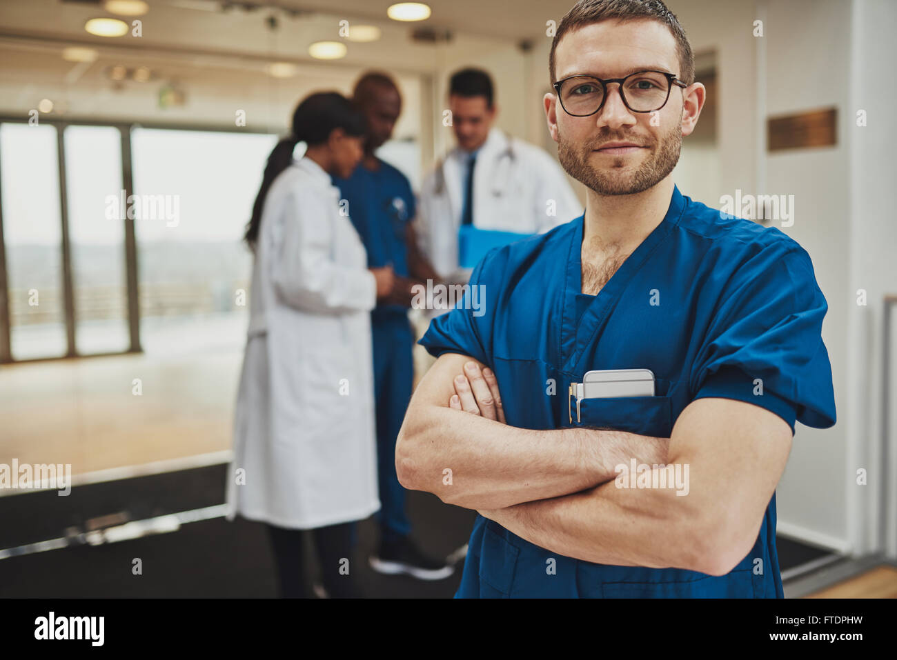 Confident relaxed surgeon doctor at hospital with team of doctors in background - Stock Image