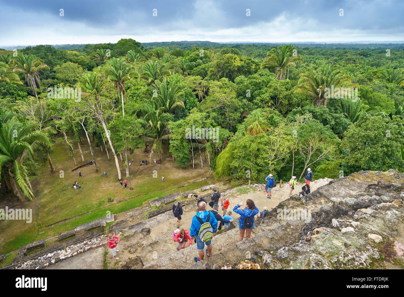 Tourists admiring the view of Yucatan from the top of High Temple, Ancient  Maya Ruins, Lamanai, Belize - Stock Image
