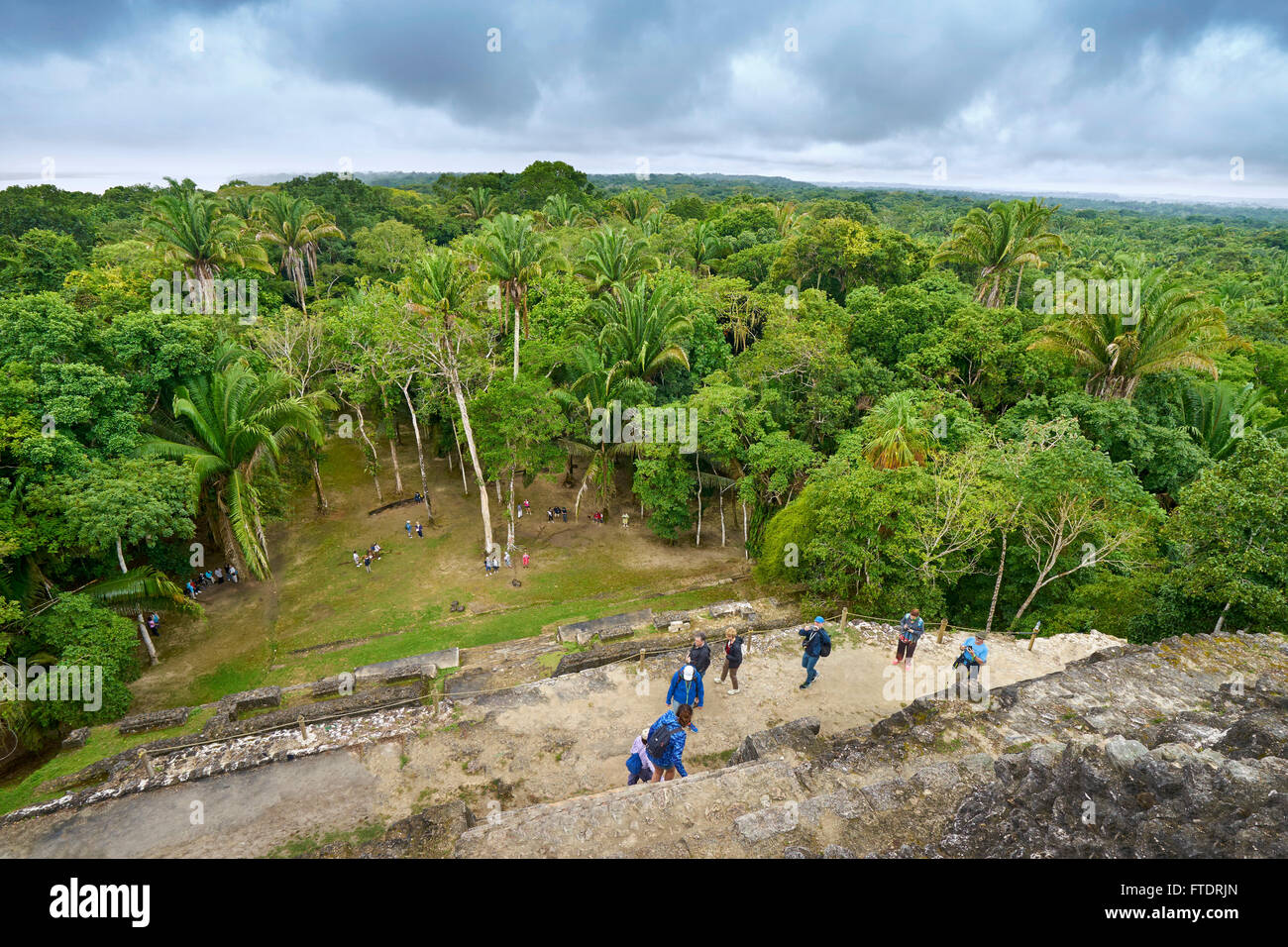 Tourists admiring view of Yucatan from the top of High Temple, Ancient  Maya Ruins, Lamanai, Belize - Stock Image
