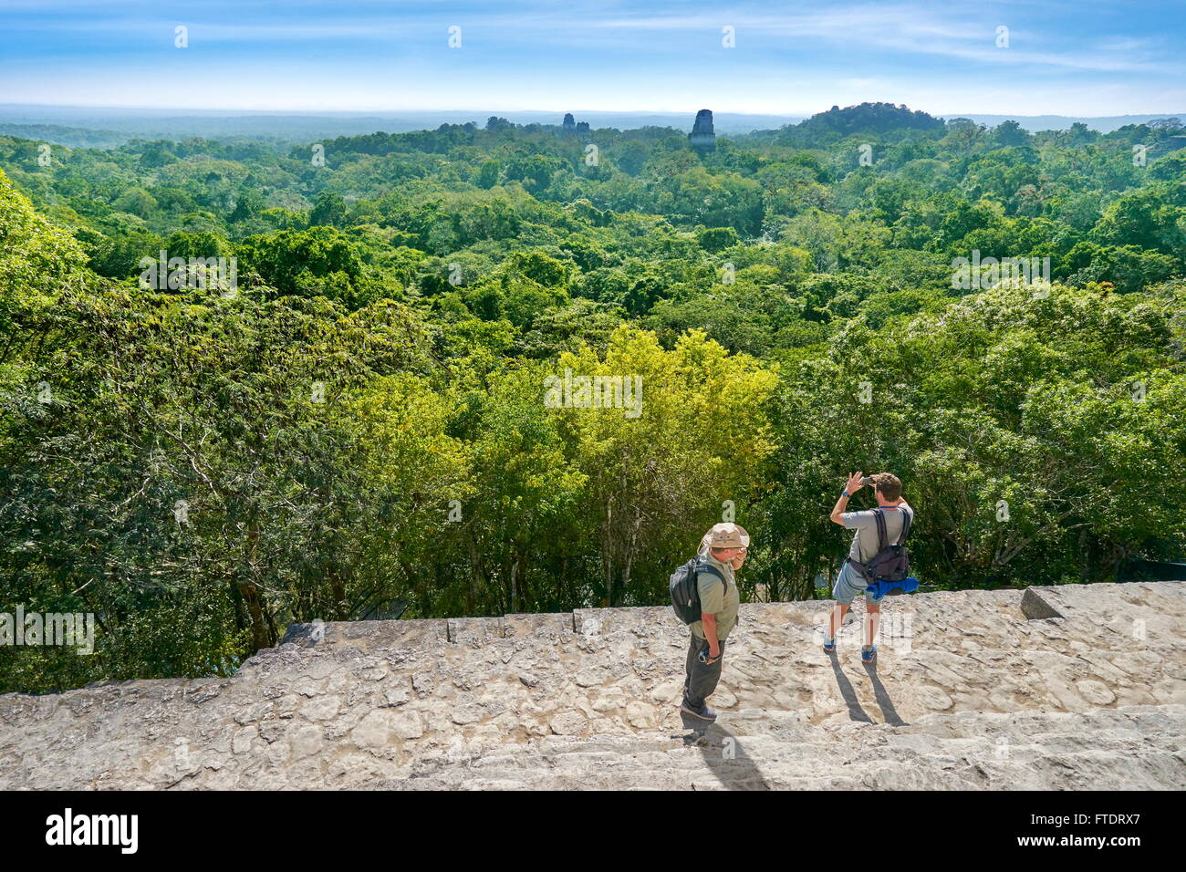 Tourists on the top of Temple IV, Ancient Maya Ruins, Tikal National Park, Yucatan, Guatemala - Stock Image