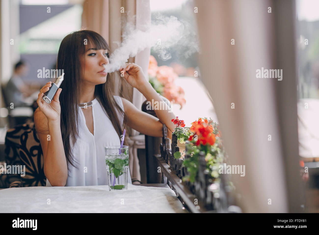 girn in cafe with E-Cigarette - Stock Image