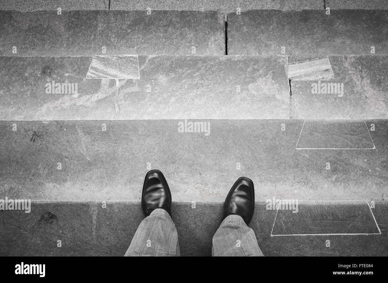 Urbanite man in black new shining leather shoes standing on outdoor stone stairs - Stock Image