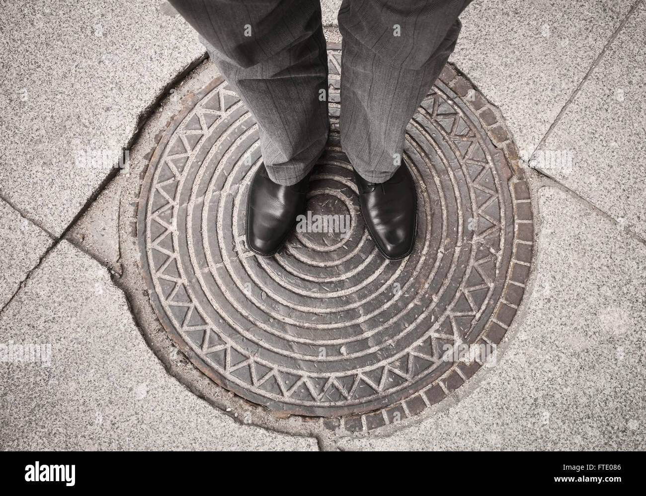 Urbanite man in black new shining leather shoes standing on rusty sewer manhole - Stock Image
