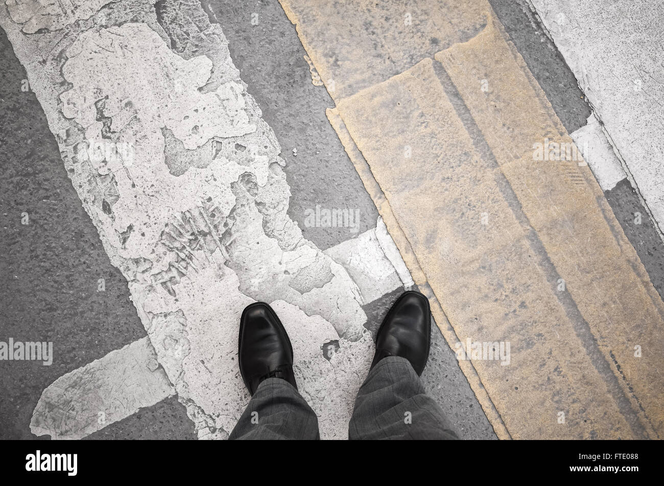 Urbanite man in black new shining leather shoes standing on the dirty pedestrian crossing road marking - Stock Image