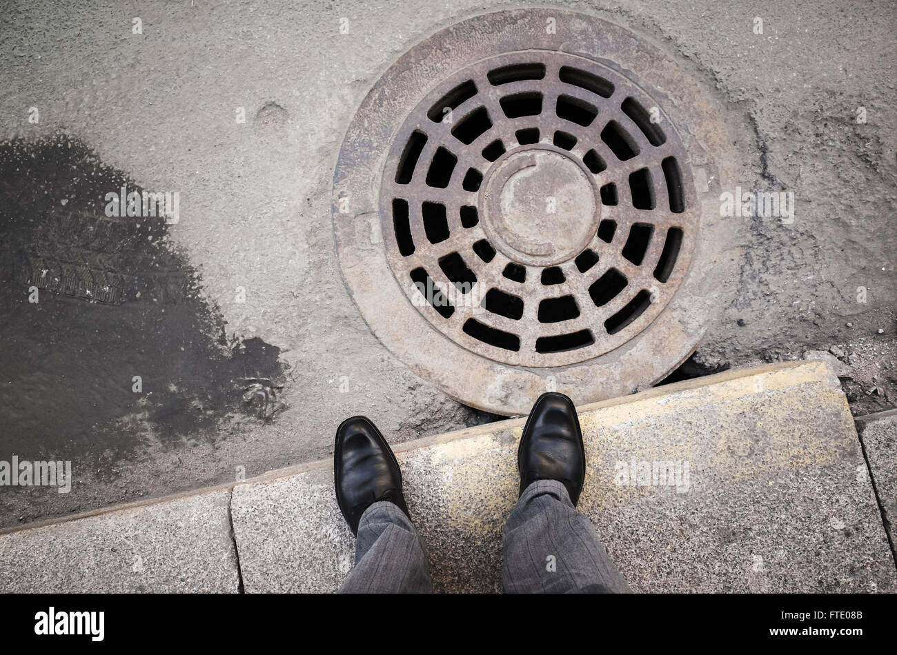 Urbanite man in black new shining leather shoes standing on the roadside near rusty sewer manhole - Stock Image