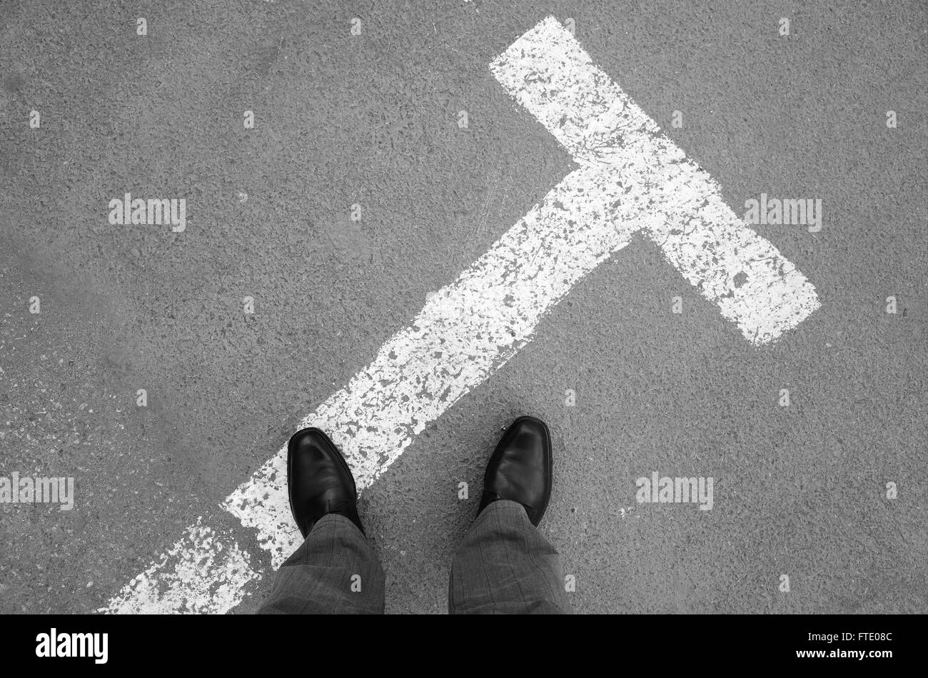Urbanite man in black new shining leather shoes standing on asphalt pavement with parking lot road marking - Stock Image