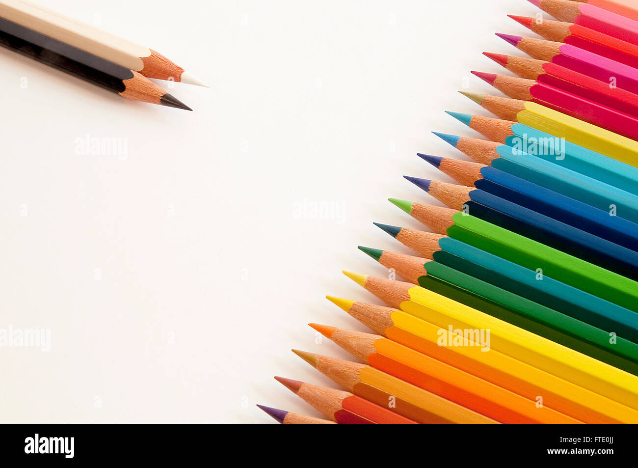 Black and white pencils opposite colored pencils. - Stock Image