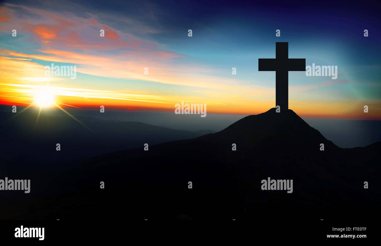 Christianity concept with christian cross silhouette on the hill on sunset - Stock Image
