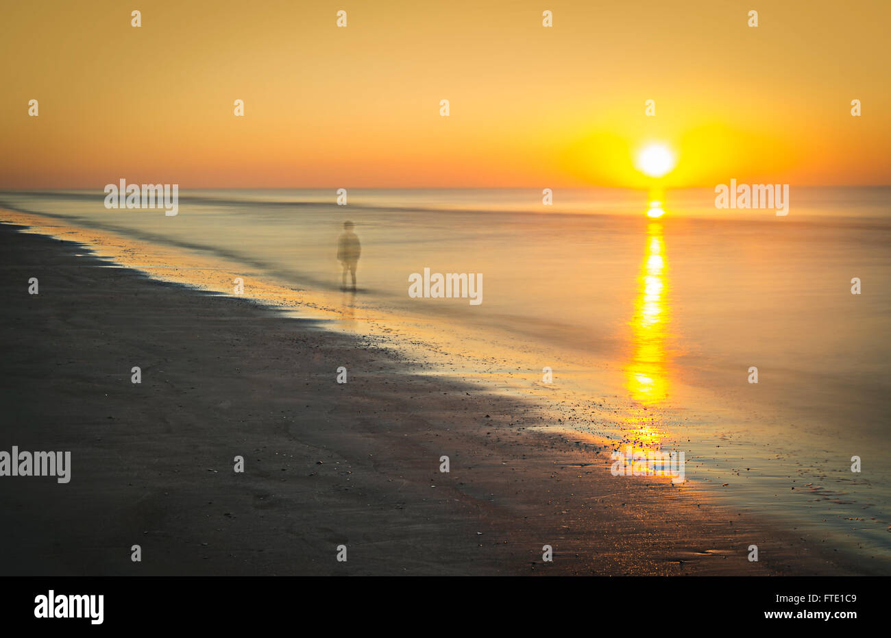 Sad Ghostly Person Walking On Beach At Sunset - Stock Image