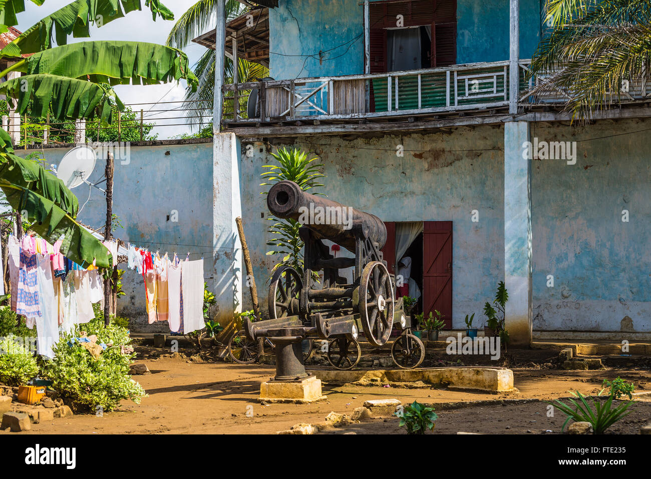 Old cannon in the courtyard of an apartment house in the town of Hell Ville, Nosy Be - Stock Image
