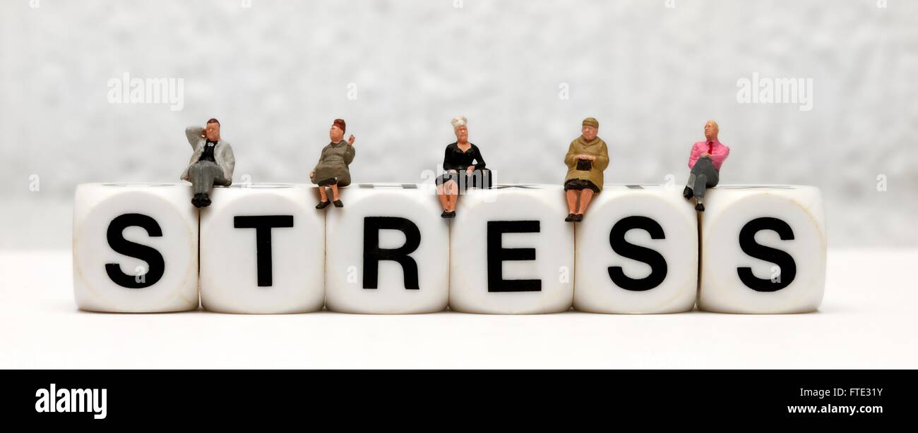 Miniature figurines sitting on top of the word stress - Stock Image