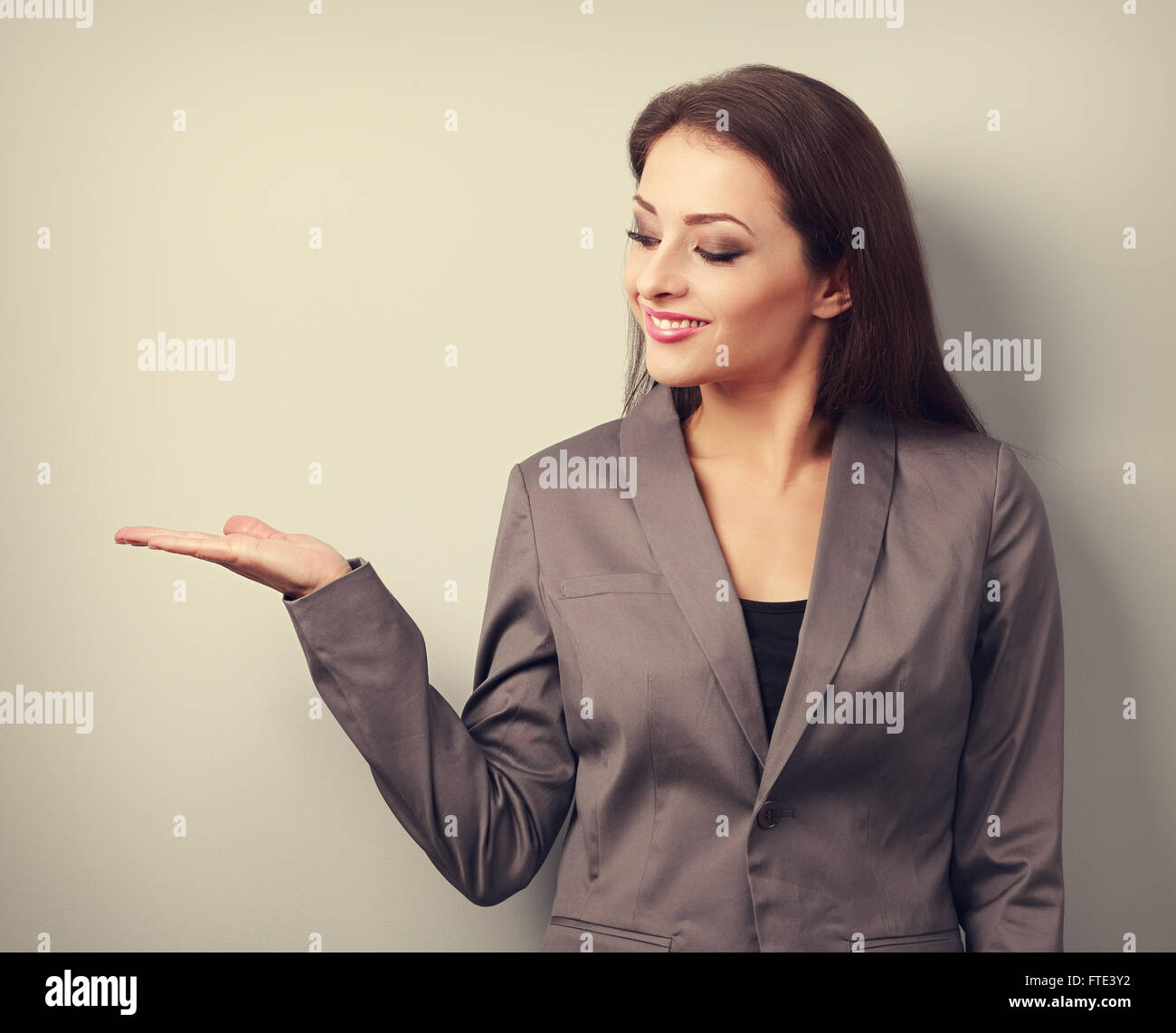 Happy business woman holding something empty in hand and demonstration. Toned portrait - Stock Image