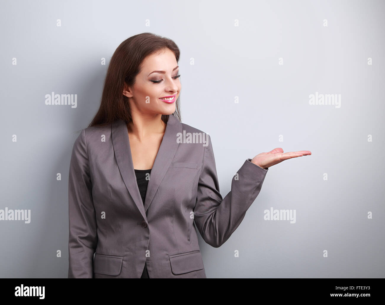 Happy business woman holding something empty in hand and demonstration on blue background - Stock Image