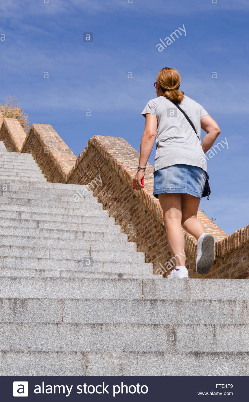An adult woman wearing miniskirt walks up the stairs with an smartphone - Stock Image