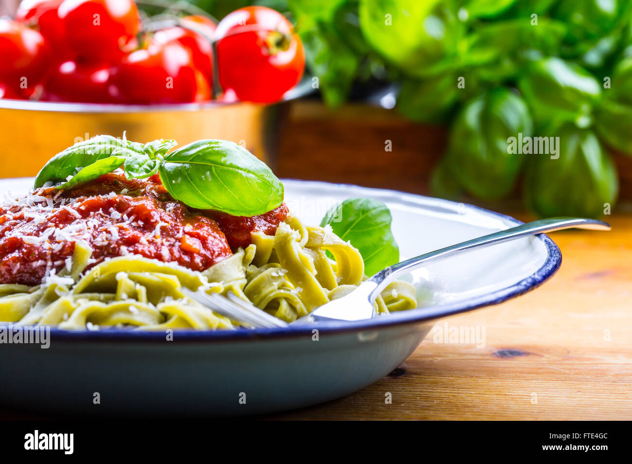 Pasta. Italian and Mediterranean cuisine. Pasta Fettuccine with tomato sauce basil leaves garlic and parmesan cheese. - Stock Image