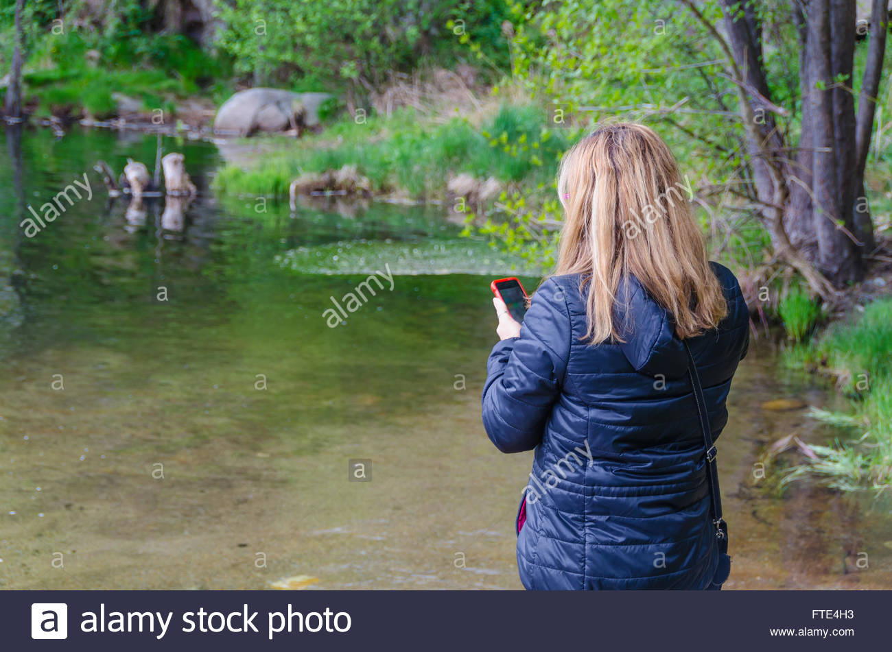 Woman searching network coverage in a river - Stock Image