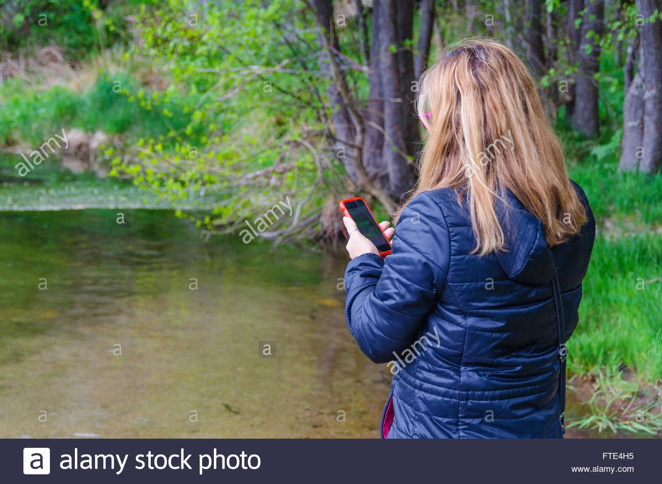 Woman searching network coverage near a river. Connectivity and telecommunications concept - Stock Image