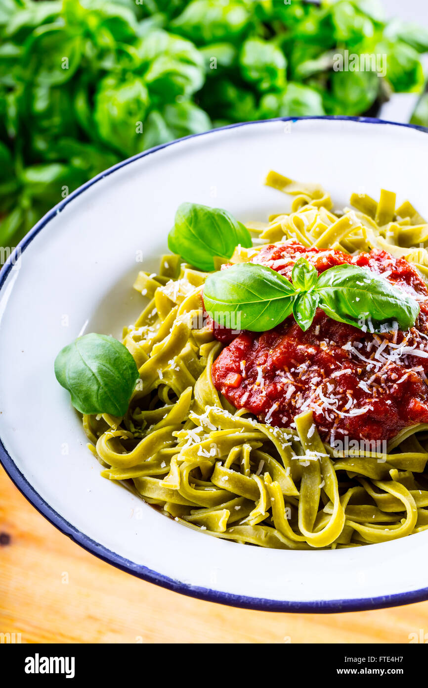 Pasta. Italian and Mediterranean cuisine. Pasta Fettuccine with tomato sauce basil leaves garlic and parmesan cheese. Stock Photo