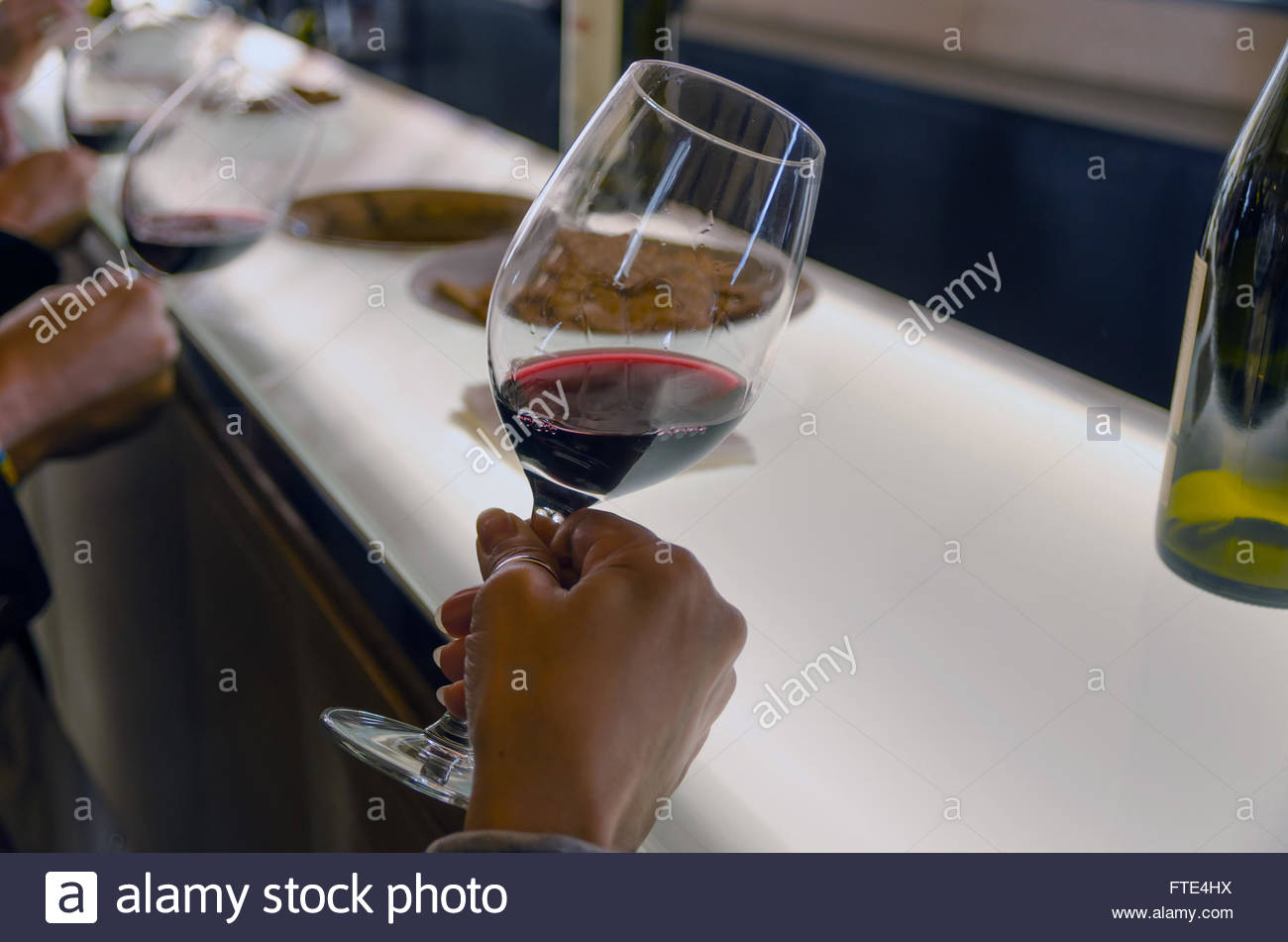 Some people are holding red wine cups in a wine tasting to see the wine transparency - Stock Image