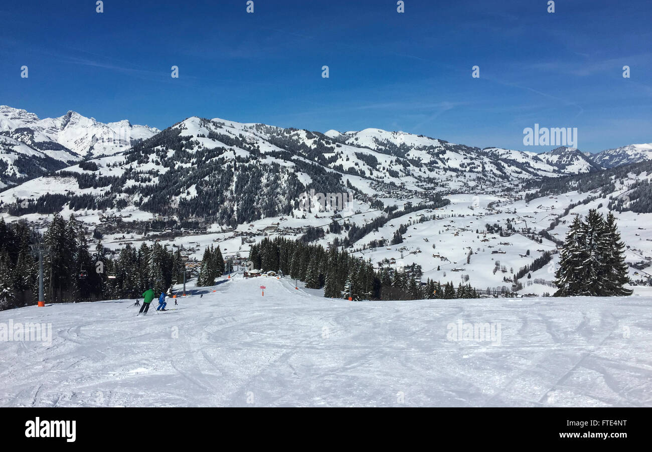 Skiing slope in the Gstaad winter sport area. In the background mountains and the village of Schönried. Gstaad, - Stock Image