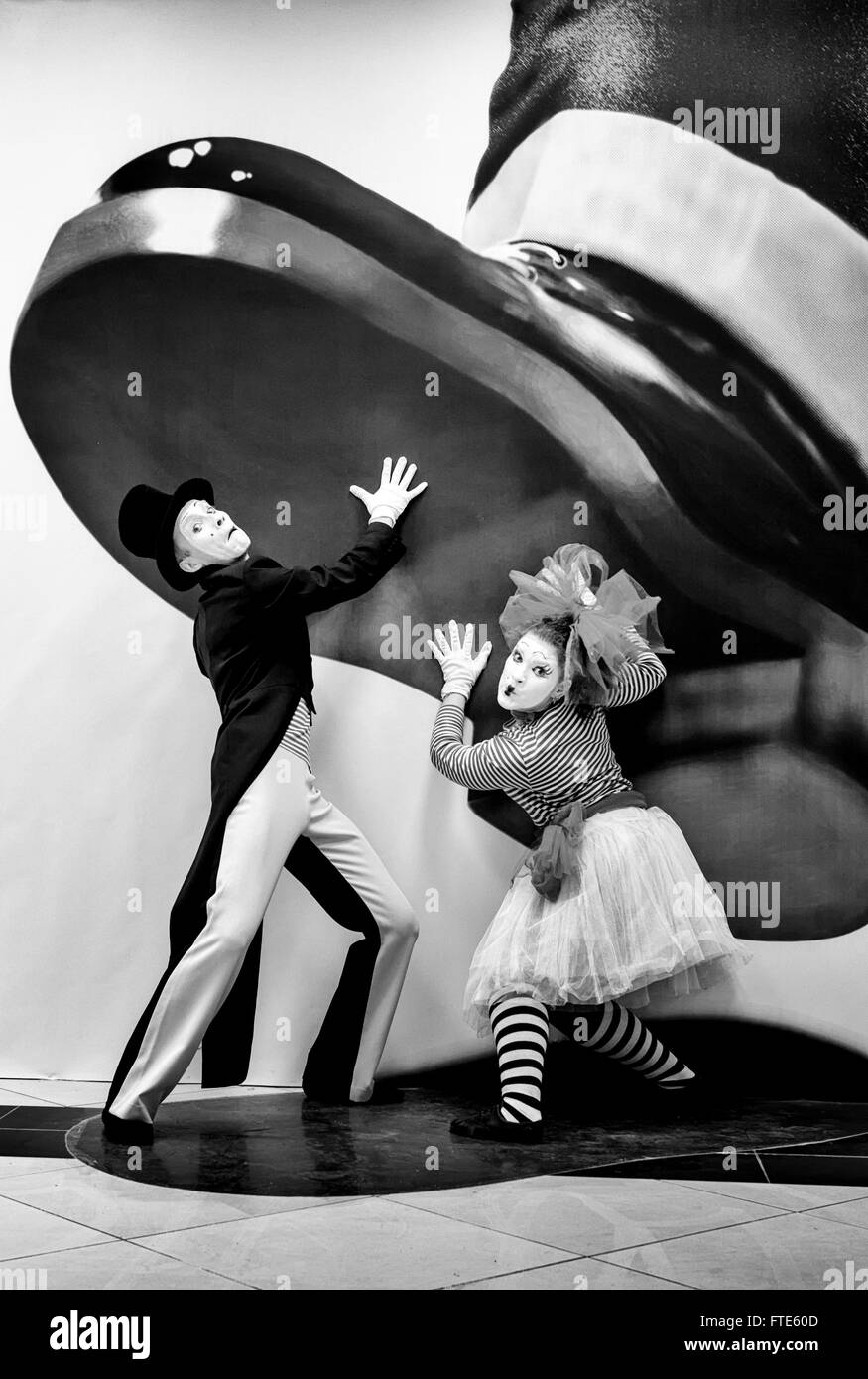 UFA - RUSSIA 21ST FEBRUARY 2016 - Male and female mime artists pose by a giant boot for people to view in a free - Stock Image