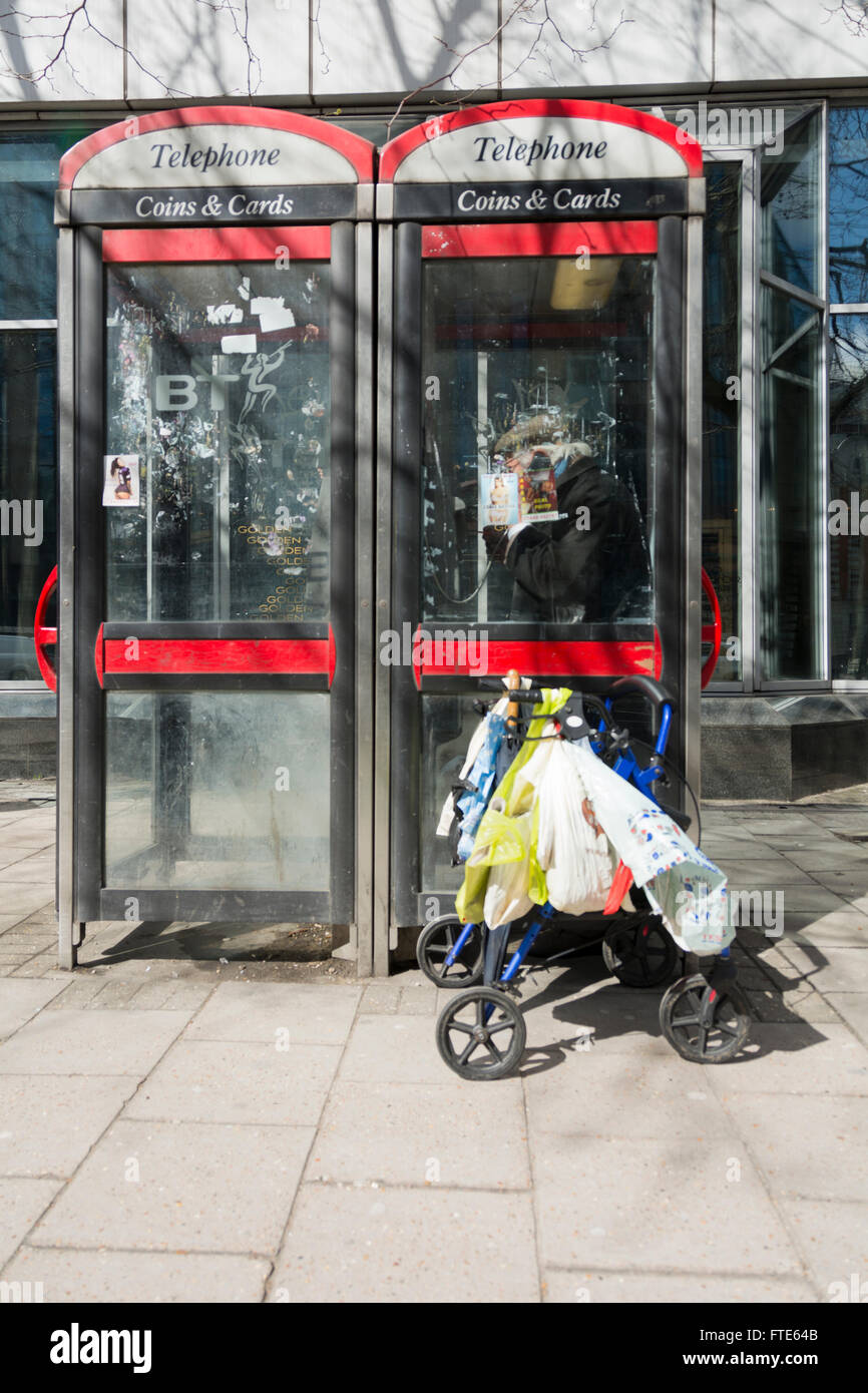 Pensioner making a telephone call in a telephone kiosk on London's Euston Road, UK - Stock Image