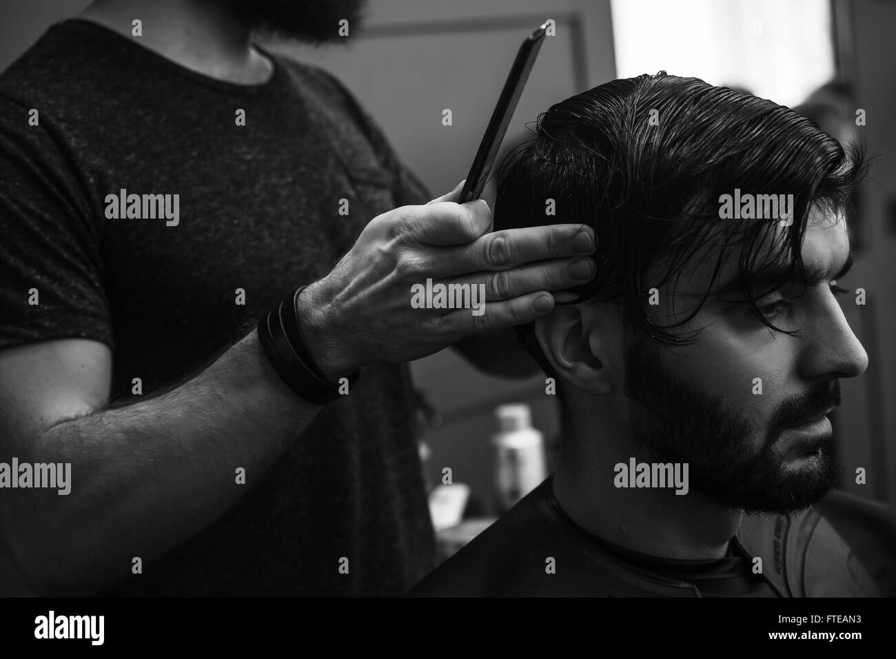 Male barber combing and shaving hair of a male client Stock Photo