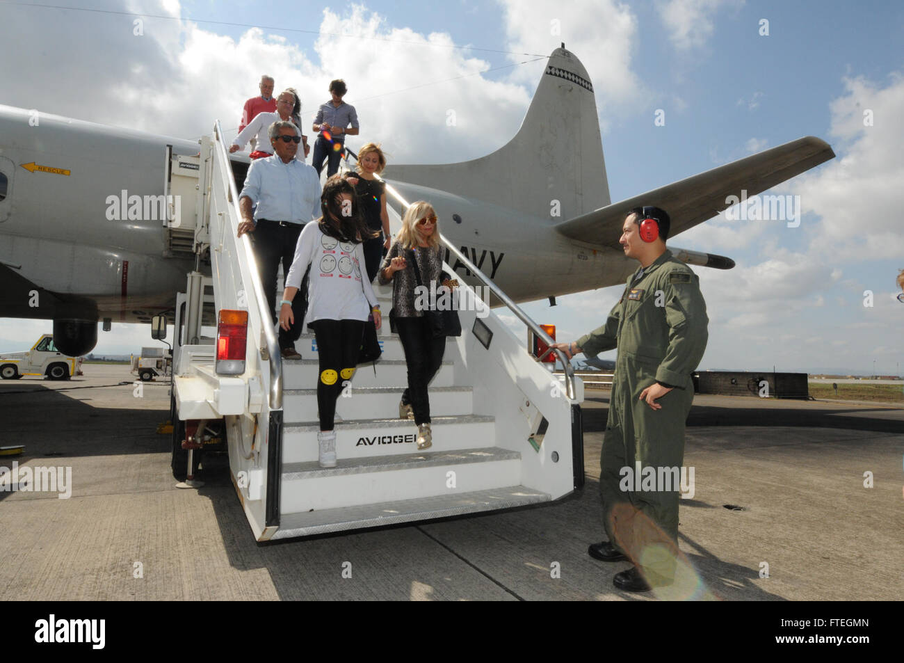 SIGONELLA, Sicily (Oct. 5, 2014) Naval Aircrewmen 2nd Class Isaac Davila helps the local chapter of the International Business Womens' Federation and  their family members as they step off  one of VP-4's P3-C Orion maritime patrol aircraft following a tour. is conducting naval operations in the U.S. 6th Fleet area of operations in support of U.S. national security interests in Europe. Stock Photo