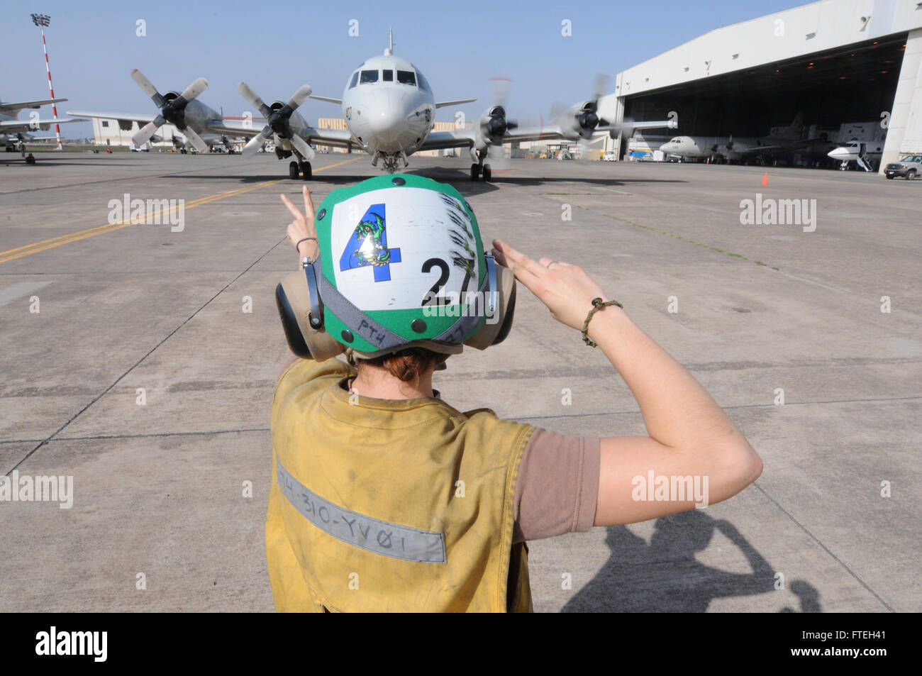 SIGONELLA, Sicily (Oct. 10, 2014) - Aviation Structural Mechanic 2nd Class Margaret Mele signals a P-3C Orion maritime - Stock Image