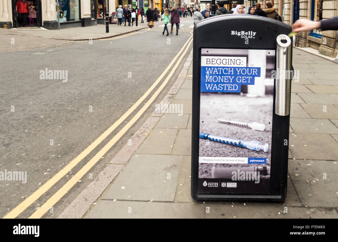 Person's hand operating litter bin which is adorned with anti begging adverts by Nottingham City Council (Labour) - Stock Image