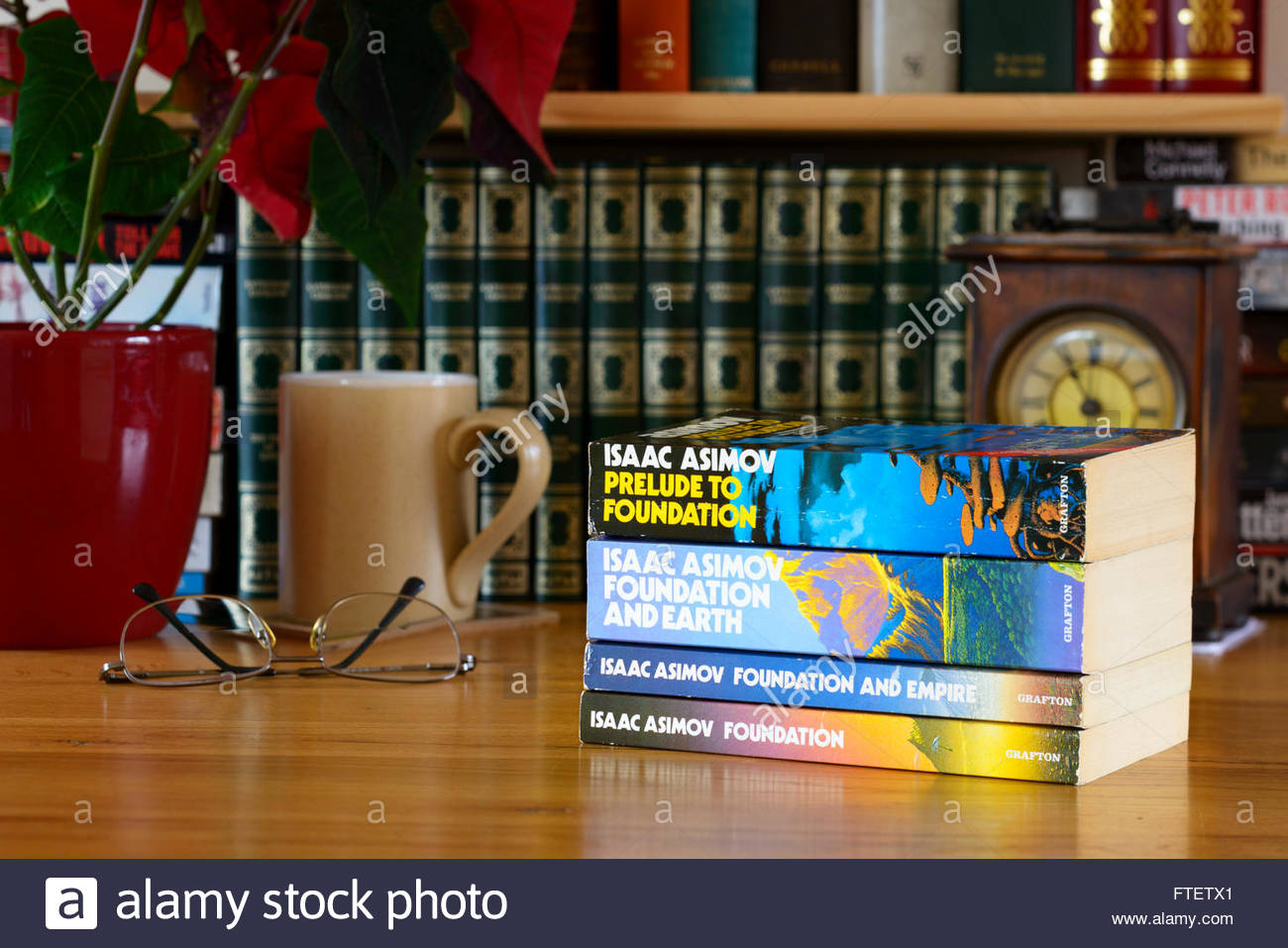 Isaac Asimov book titles, stacked on desk, England - Stock Image