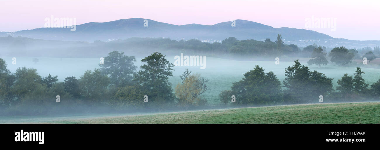 Mist is rising on the fields in front of the Malvern Hills, Worcestershire at dawn. Stock Photo
