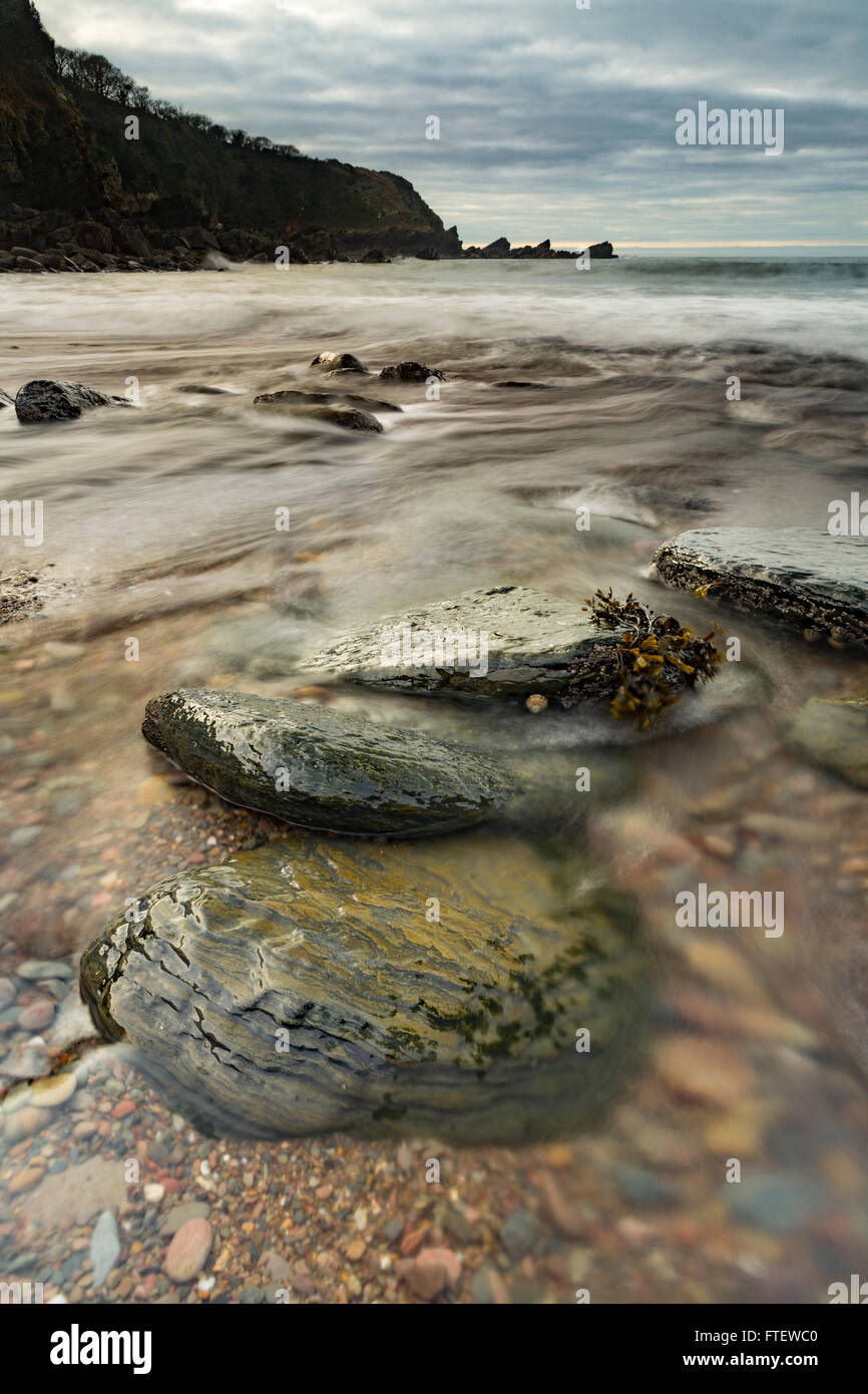Lee Bay Beach, Devon, England, reveals beautiful rocks and pebbles as the sea recedes at low tide. Stock Photo