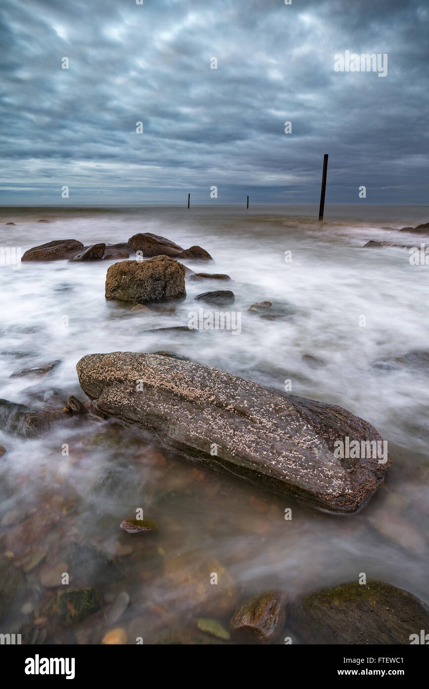 Lynmouth Beach, Devon, England, is covered in rocks and pebbles. When the sea comes in the waves swirl around the Stock Photo