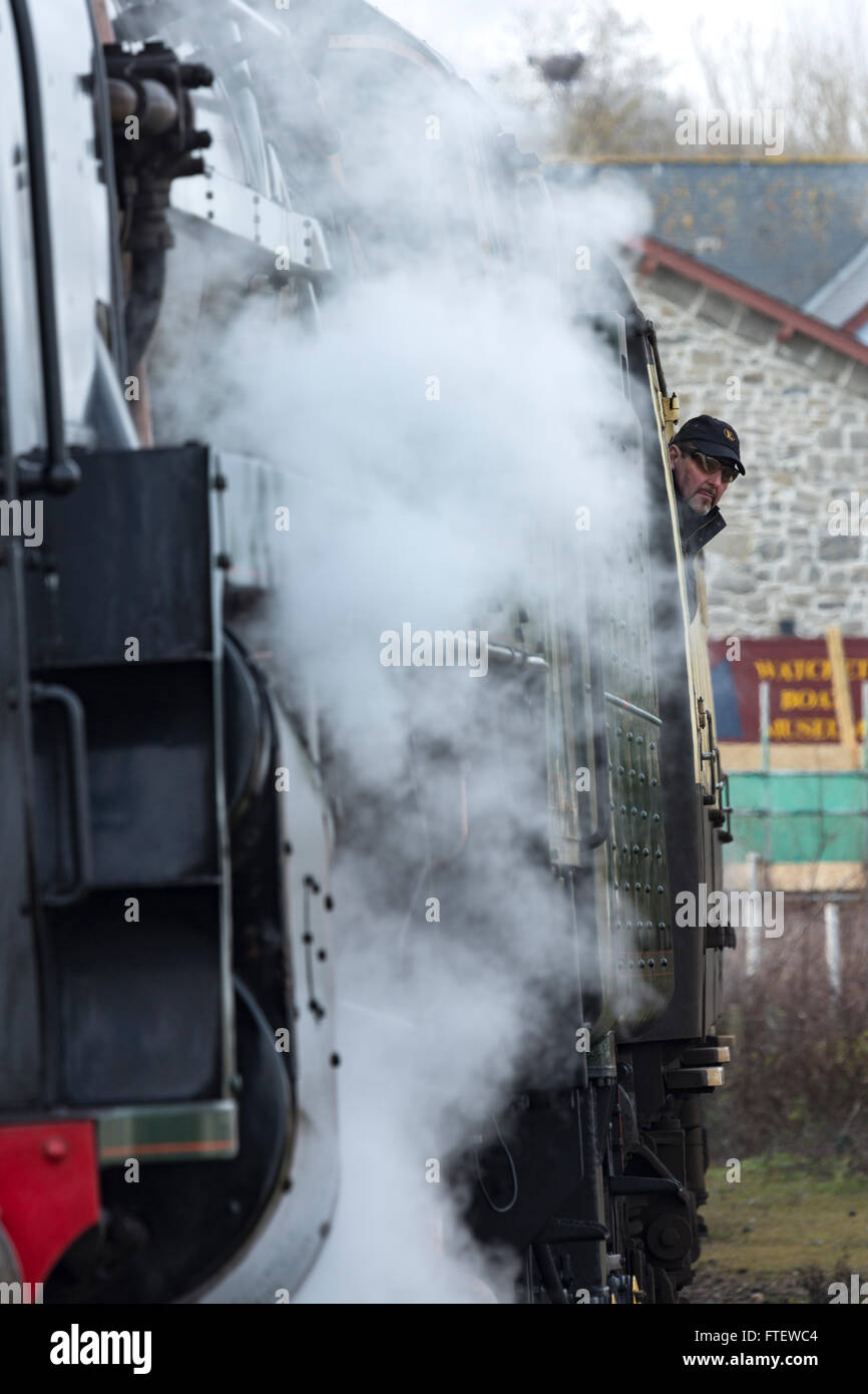 A male passenger looks out of the steam Train, Pines Express, 92214, as it leaves the station at Watchet, Somerset, Stock Photo