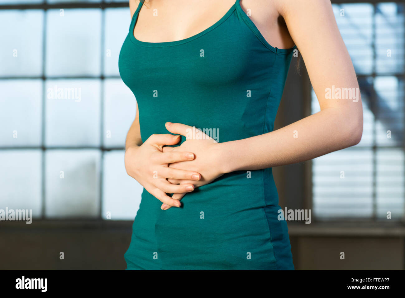 Close up of a young woman hands on tummy Stock Photo