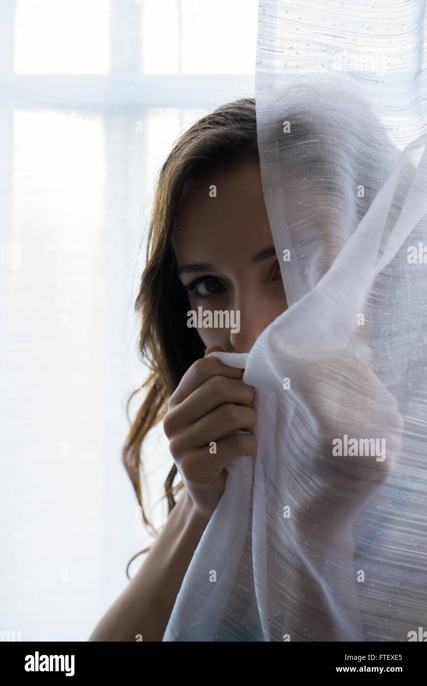 Serious young woman hiding behind the curtains by the window - Stock Image