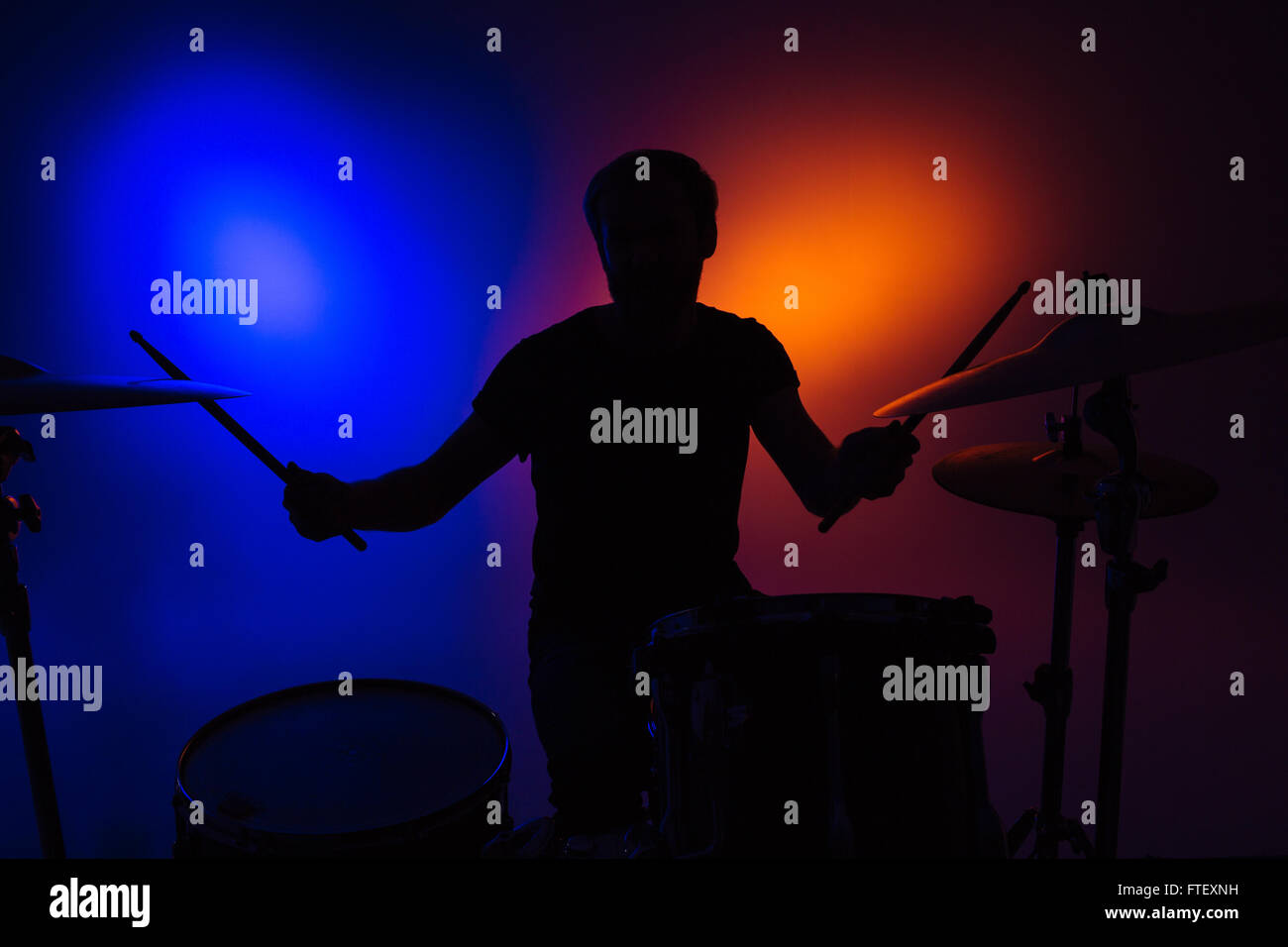 Silhouette of man drummer sitting and playing drums with sticks over colorful backgound - Stock Image
