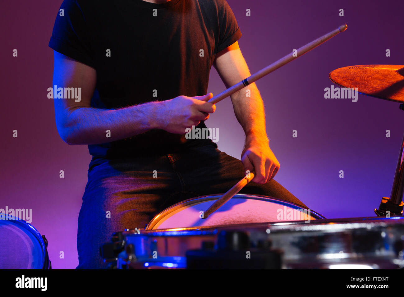 Closeup of hands of man drummer sitting and playing drums with drumsticks over dark background - Stock Image