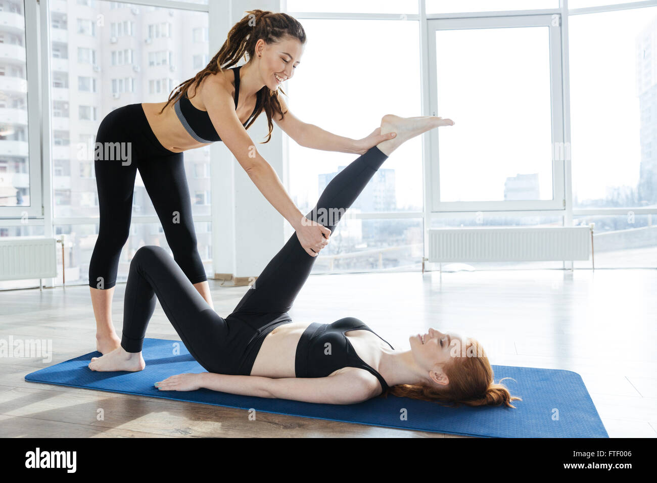 Happy pretty young woman stretching legs with personal trainer - Stock Image
