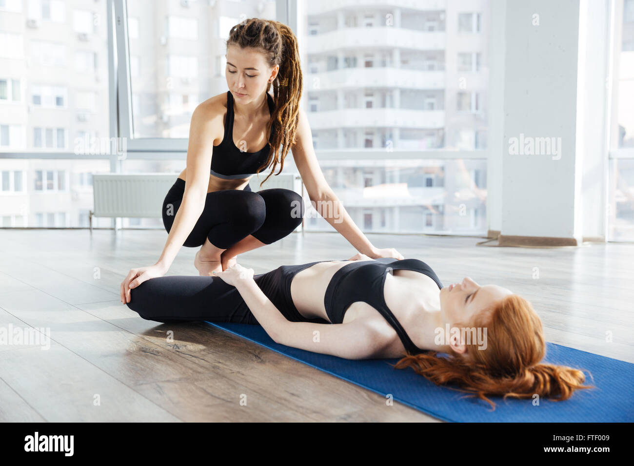 Female trainer stretching legs of redhead young woman lying on the floor in yoga studio - Stock Image