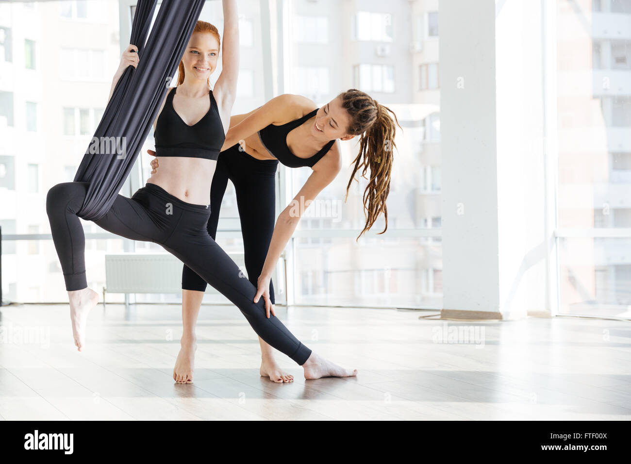 Happy pretty young woman doing aerial yoga with trainer in studio - Stock Image