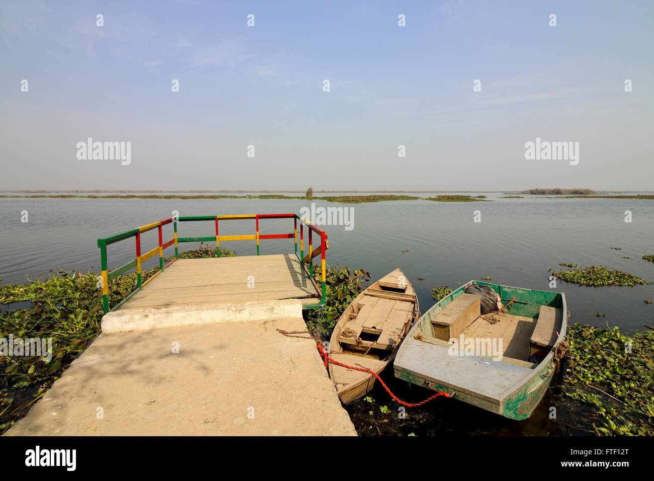 Small boats moored at the colorful jetty at Harike wetlands wildlife reserve in Punjab, India. - Stock Image