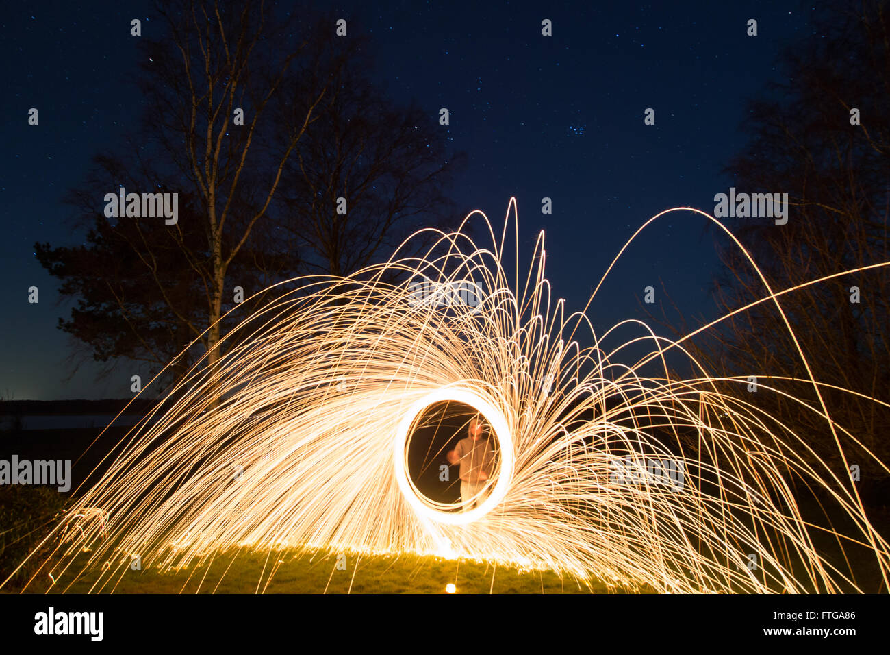 A young man performing steel wool photography. Stock Photo