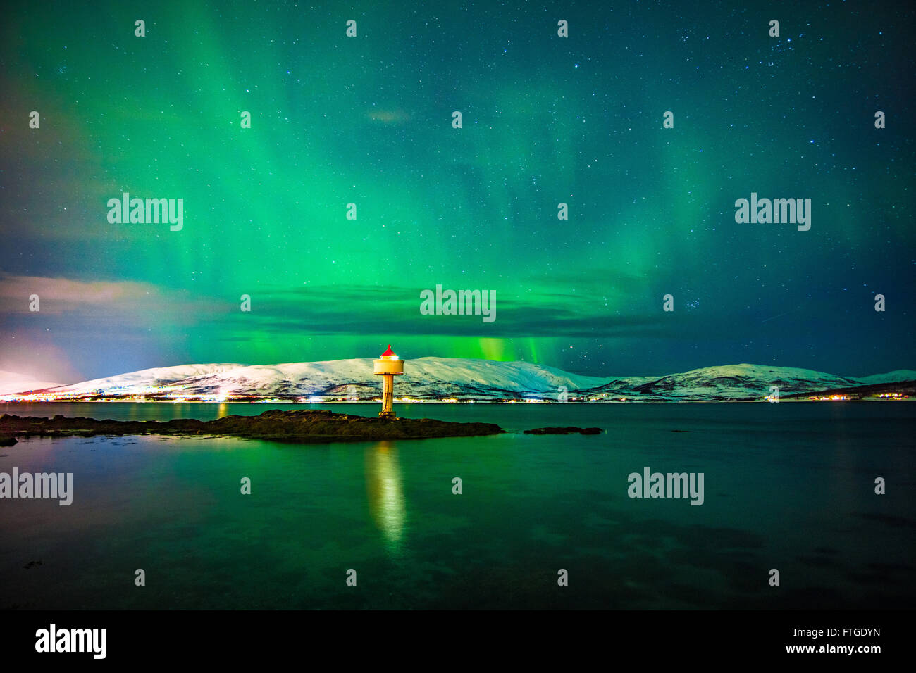 Aurora Borealis dancing over fjord, Tromso Northern Norway - Stock Image