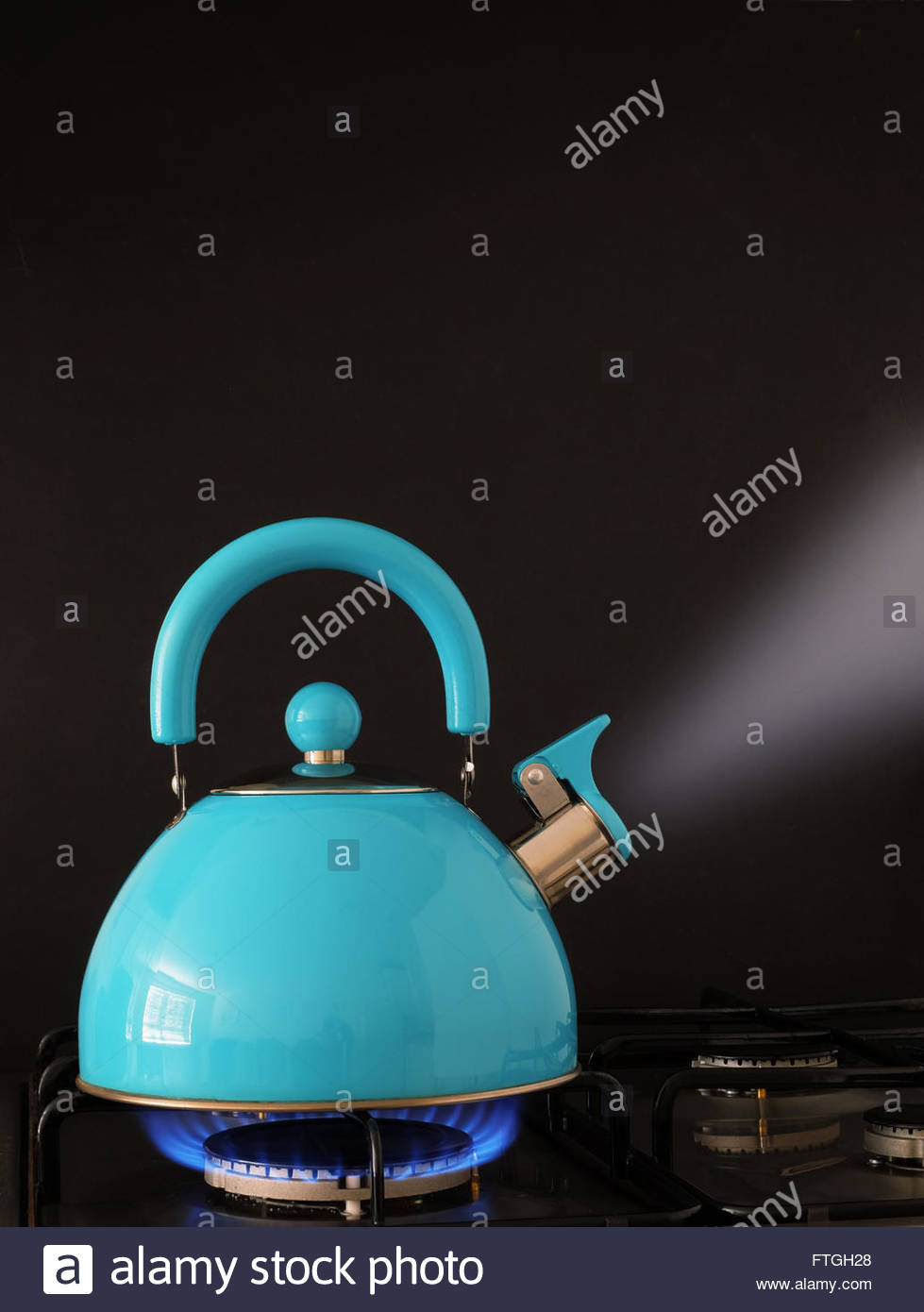 Kettle boiling water on a gas flame kitchen hob - Stock Image