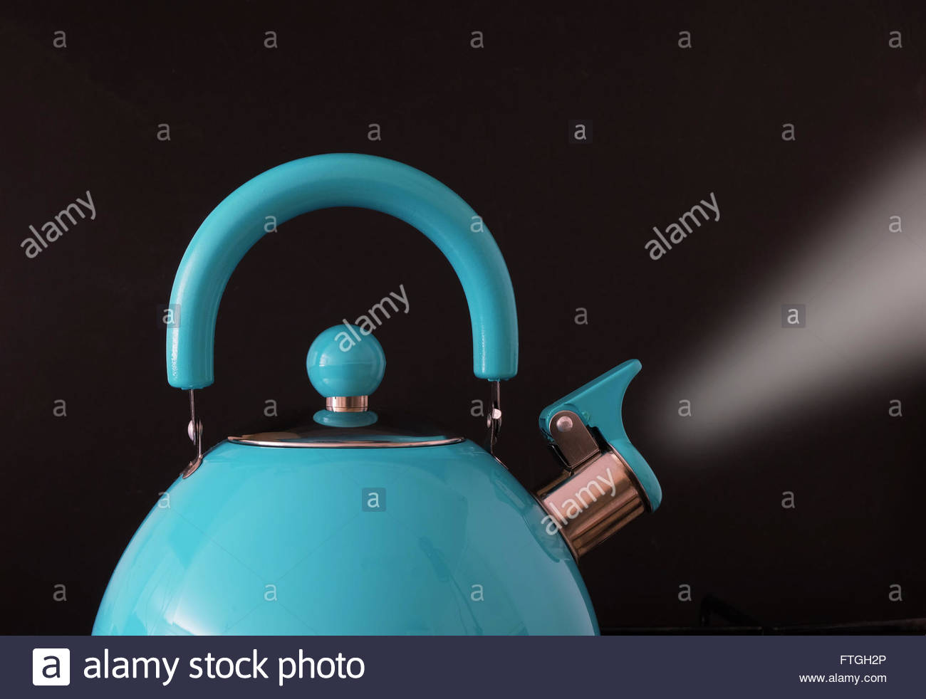 Closeup of boiling kettle steam coming from the spout against black background - Stock Image