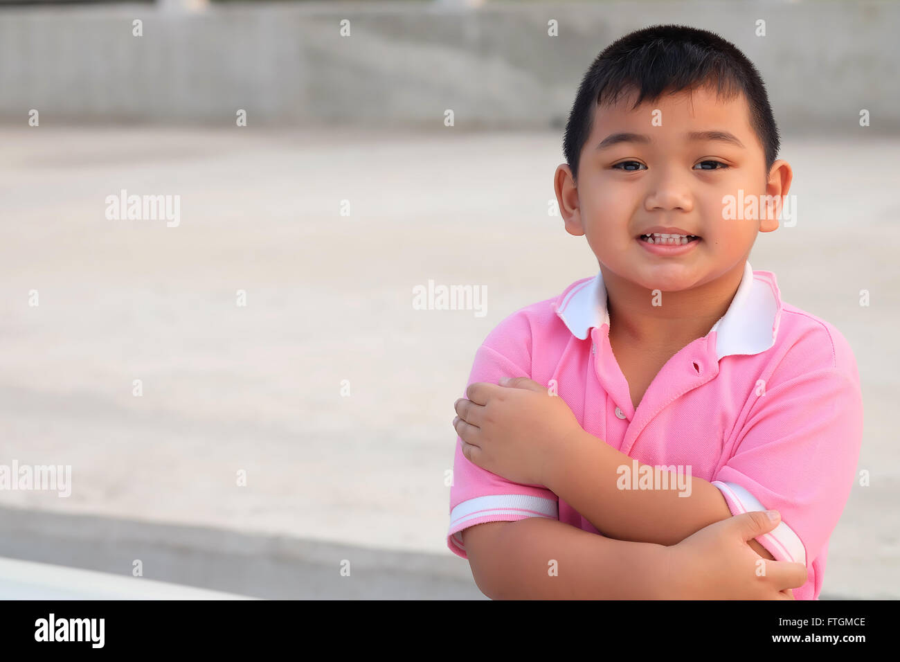 Kid portrait smiling and cross one's arm  - Asia children - Stock Image