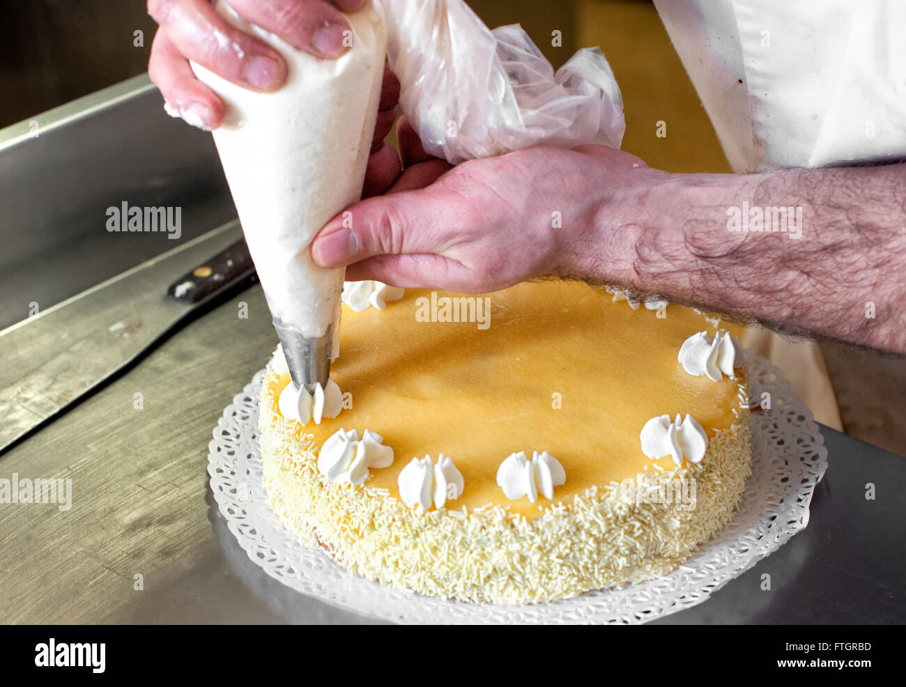 Baker piping cream decorations on to the top of a cake using a nozzle and bag, close up of his hands and the cake - Stock Image