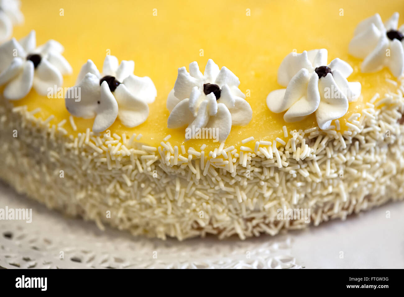 High Angle Close Up Culinary Still Life of Homemade Lemon Cake Decorated with Icing Flowers and Coconut Sprinkles - Stock Image